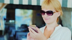 Female tourist using a mobile phone on the background of shop window Stock Footage