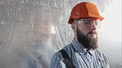 Young bearded engineer builder in a protective helmet and goggles on background Stock Footage