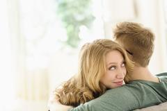 Young woman looking over boyfriend's shoulder - stock photo