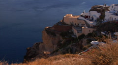 Cave houses in Oia village in evening light next to the Santorini caldera. Stock Footage
