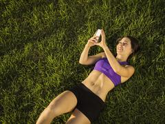 Young woman lying on grass using phone - stock photo