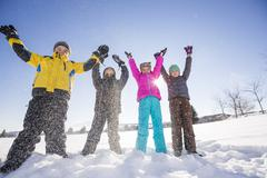 Children (8-9, 10-11) standing in snow with arms raised - stock photo