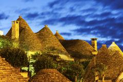 Traditional roofs of trulli houses at sunset Stock Photos