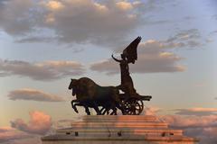 Statue of goddess Victoria on Altare della Patria at sunset - stock photo