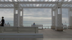 A white sunshade construction with white benches on Promenade des Anglais, Nice Stock Footage