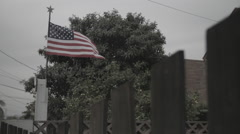 American Flag Blowing Behind Picket Fence - Film Log Stock Footage