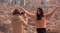 Unidentified girl pose against aerial cityscape, other take pictures Stock Footage
