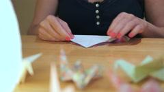 Girl start Folding a Crane Origami Stock Footage