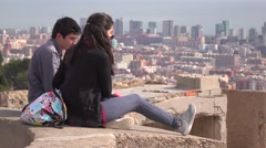 Young couple sit against aerial cityscape, impressive Barcelona panorama Stock Footage