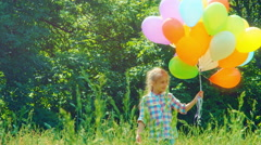 Preschooler girl walking with balloons and in the park - stock footage