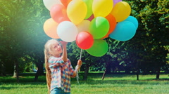Preschooler girl waving hand and playing with balloons - stock footage