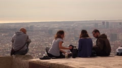 Four friends rest on edge above city, aerial Barcelona view on background. Stock Footage