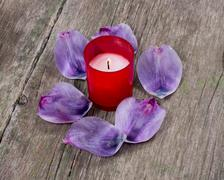 The red burning candle surrounded with lilac petals Stock Photos