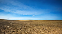 4k Timelapse of plowed field under blue sky with clouds Stock Footage