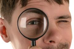 Man looking through a magnifying glass closeup Stock Photos