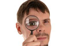 Man looking through a magnifying glass giant eye Stock Photos