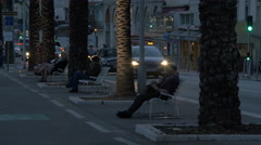 Sitting on benches at the promenade in Nice in the evening Stock Footage