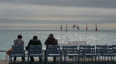 Three people sitting on blue chairs along Promenade des Anglais, Nice Stock Footage