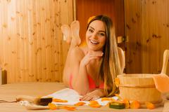 Young woman relaxing in sauna. Spa wellbeing. - stock photo