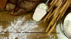 Bread, sheaf of wheat ears and flour  on a wooden table, dolly, top view Stock Footage