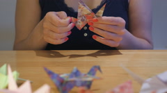 Girl Finishing a Crane Origami Stock Footage