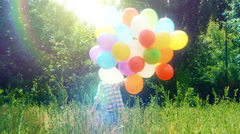 Preschooler girl walking with balloons and in the park and waving hand - stock footage