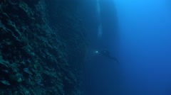 Scuba diver in a wall of reef with light. Deep blue background. Stock Footage