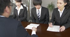 Japanese employer talks to job candidates about contracts at job interview Stock Footage