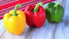 Woman hand placing yellow, red and green capsicum on a wooden table - stock footage