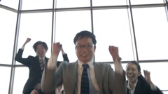 Japanese boss jumps with the team to celebrate the win in Business Stock Footage