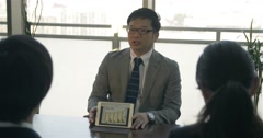 Japanese business man explains graphs to clients Stock Footage