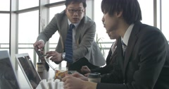 Japanese Boss works with junior staff on a project Stock Footage