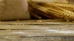 Grains of golden wheat in a sack spilling on the old wooden background Stock Footage