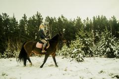 Caucasian woman riding horse on snowy path - stock photo