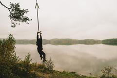 Man hanging on rope swing at remote lake Stock Photos