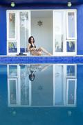 Mixed race woman reflected in swimming pool - stock photo