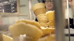Woman Stacks Fresh Made Waffle Cones Inside Display Case In Local Ice Cream Shop - stock footage