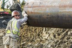 Caucasian worker hauling pipe at construction site Stock Photos