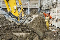 Caucasian worker directing digger at construction site Stock Photos