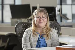 Caucasian businesswoman with Down Syndrome smiling in office Stock Photos