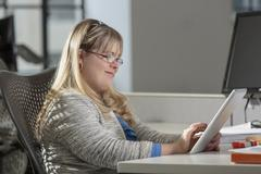 Caucasian businesswoman with Down Syndrome using digital tablet in office Stock Photos