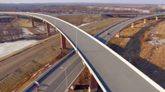 Brand new highway overpass construction project, dynamic aerial flyover view Stock Footage