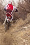 Motorcyclist riding dirt bike on rural path Stock Photos