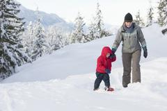 Caucasian mother and son snowshoeing on hillside Stock Photos