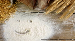 Scene with smiley face over sieved flour, wheat and bread, dolly Stock Footage