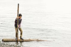 Mixed race boy playing on log in lake Stock Photos