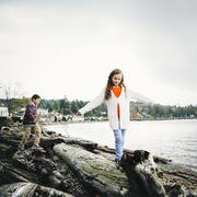 Mixed race children climbing on logs at lake - stock photo