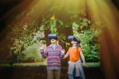 Mixed race children using virtual reality goggles outdoors - stock photo