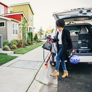 Mixed race woman unpacking car Stock Photos