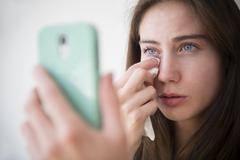 Native American woman with cell phone wiping away tears Stock Photos